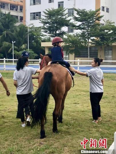 孤独症儿童在老师指导下进行马术训练。 王祖敏 摄