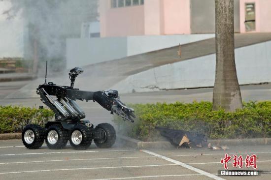 """11月8日,澳门警察总局联合中国人民解放军驻澳部队,协调多个部门及机构进行代号""""灵犬"""" 的大型联合反恐演练。图为治安警察局在停车场发现炸弹及进行排爆。中新社发 钟欣 摄"""