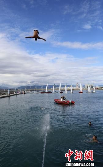 11月28日,2018三亚国际海上极限跳水大师赛在三亚半山半岛帆船港居高起跳。图为选手从27米高的跳台一跃而下瞬间。 王晓斌 摄