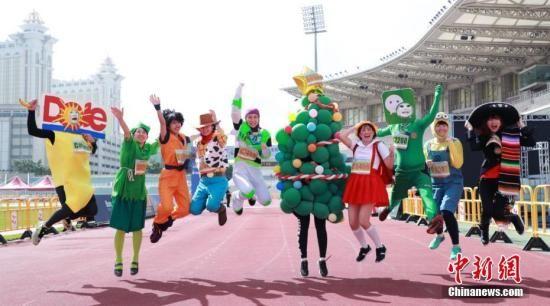 """资料图:""""2018澳门银河娱乐国际马拉松""""在奥林匹克体育中心运动场起跑。图为部分选手穿上创意服装吸引眼球。中新社发 钟欣 摄"""