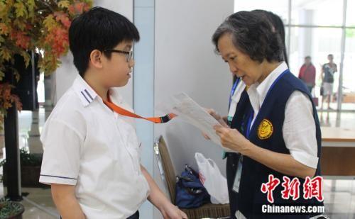 图为监考老师认真检查考生的证件。刘雨浓 供图