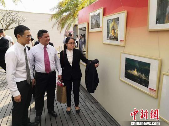 图为缅甸驻南宁总领事馆总领事梭岱南(左二)向三亚市副市长周俊(左一)介绍摄影展作品。 杨陈 摄