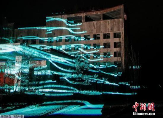 """当地时间2018年11月22日,乌克兰普里皮亚季,参观者们在切尔诺贝利核电站附近观看一场""""人工""""数字雕塑的展示。"""