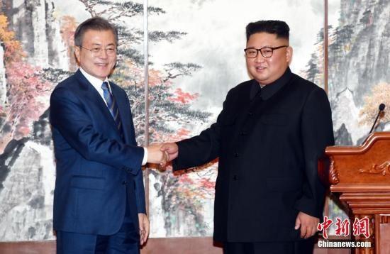 2018年9月19日,在朝鲜平壤,朝鲜国务委员会委员长金正恩(右)与韩国总统文在寅在举行共同记者会后握手。正在平壤访问的文在寅19日上午在百花园迎宾馆与金正恩举行第二轮会谈。会谈结束后,双方签署《9月平壤共同宣言》,就早日推动半岛无核化进程、加强南北交流与合作达成一致。中新社发 平壤联合采访团供图