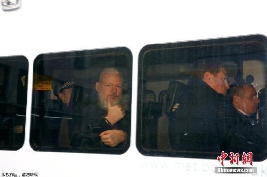 图为维基解密创始人阿桑奇在警车内向媒体竖拇指。