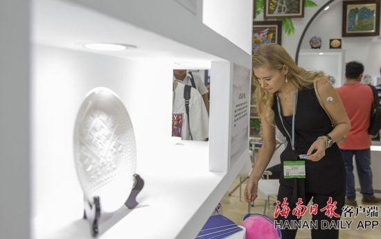 """2019年5月16日,在海南展馆内,一位外国观众被手工制作的""""南海贝雕""""吸引。南海贝瓷的原材料除了粘土外,还融入南海深海贝和珍珠成分。海南日报记者 宋国强 摄"""