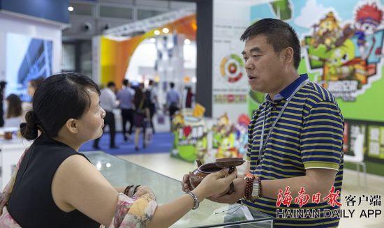 2019年5月16日,在海南展馆内,观众在观看了解一件木制茶壶。海南日报记者 宋国强 摄