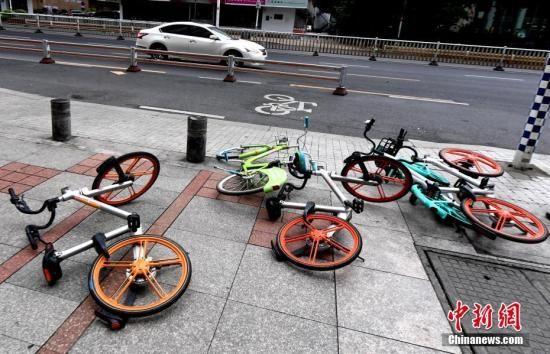 资料图:地上散落着各种品牌的共享单车。中新社记者 刘可耕 摄