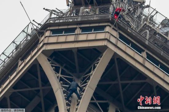 当地时间5月20日,一名男子徒手爬上法国巴黎埃菲尔铁塔高空,与警方僵持6小时后被逮捕