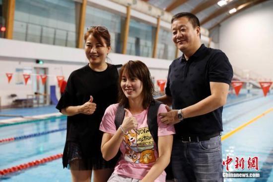 7月8日,傅园慧与父母在训练后合影留念。当日,国家游泳队在国家体育总局游泳训练馆举行公开训练课。中新社记者 韩海丹 摄