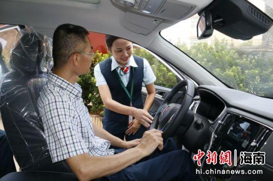 图为邮政员工为试驾客户介绍服务内容。
