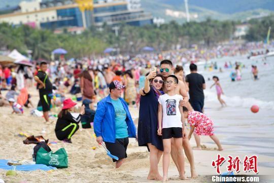 图为在三亚海滨浴场旅游的游客。 骆云飞 摄