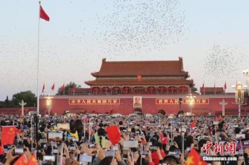 资料图:民众到天安门广场观看升旗仪式并唱响国歌。中新社记者 盛佳鹏 摄