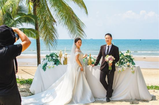 十月四日,一对情侣在三亚湾海滩拍摄婚纱照。 本报记者 武威 摄