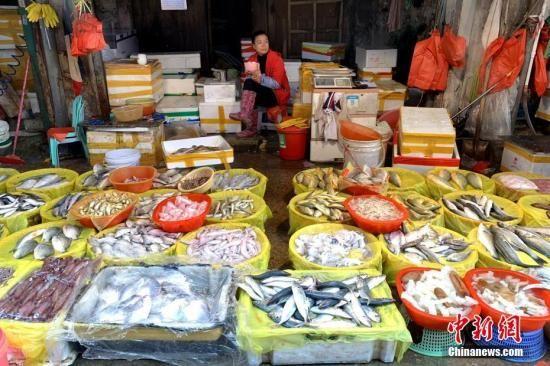 资料图片:正在等待客人的海鲜摊主。王东明 摄