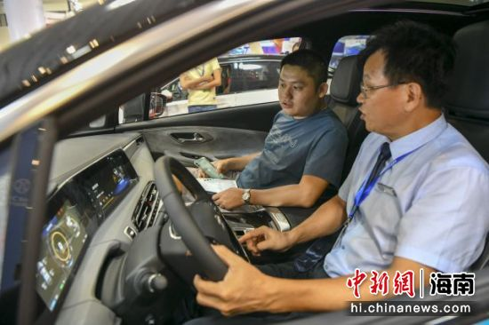 10月25日,第四届海南新能源汽车及电动车展览会在海南国际会展中心开幕。图为一位男士正在体验一款纯电新能源汽车。骆云飞摄