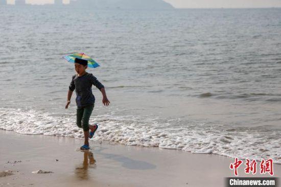 """三亚湾沙滩上,一位小朋友头戴""""伞帽""""在嬉水。(资料图) 王晓斌 摄"""