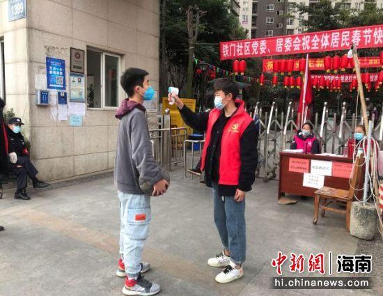 海南师范大学学子叶蕾在四川省成都市郫都区犀铁雅居社区门口做返乡人员测量体温。海师供图