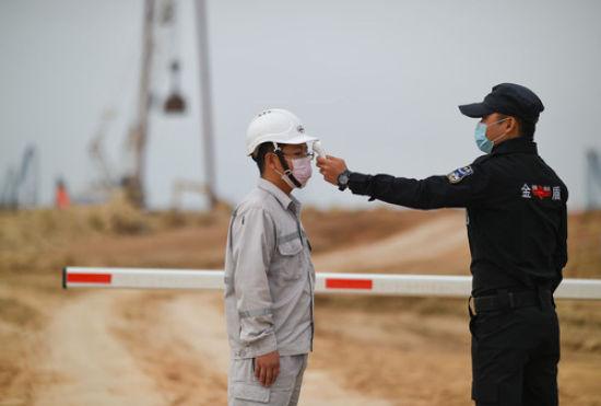 2月10日,在位于海南洋浦的海南炼化公司百万乙烯及炼油改扩建工程项目工地外,安保人员在为工地的工作人员测量体温。 新华社发(蒲晓旭 摄)
