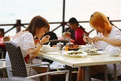3月24日,大东海景区海边,游客摘下口罩在享受美味晚餐。三亚日报记者 袁永东 摄