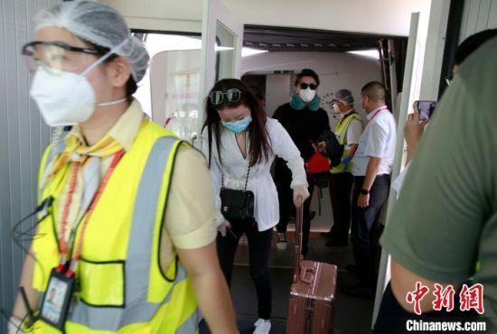 MU2527航班抵达后,戴着口罩等各类护具的旅客有序走出机舱。 记者王晓斌 摄