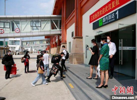 4月8日上午,武汉解除离汉通道管控后,首飞航班顺利抵达三亚。旅客经体温监测、健康码认证等防控程序后,陆续自行离场。 记者王晓斌 摄