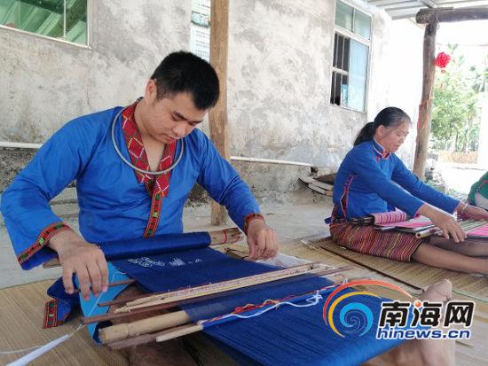 吴清裕和黎锦队的阿婆、阿姐们一起在文化棚里织锦。记者钟圆圆 摄