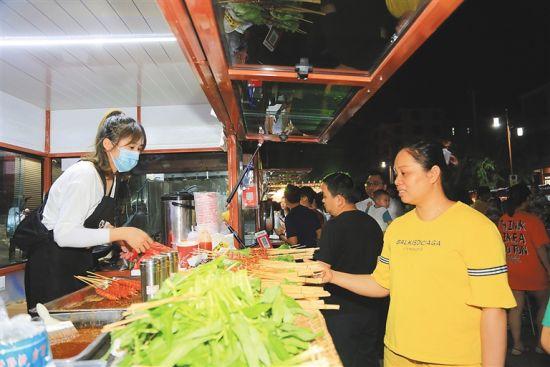 夜市的餐饮车设有备餐台、带水龙头的洗菜盆等,每个摊主都佩戴健康证牌和口罩,让消费者吃得放心。 通讯员 羊文彪 摄