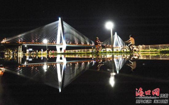 晚上,市民游客骑着共享单车在海口湾游玩。记者 王程龙 摄