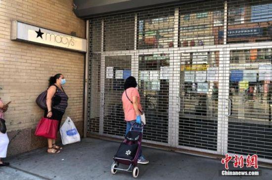 7月20日,纽约市在炎炎夏日中进入4阶段重启。按规定,商场、购物中心等在4阶段重启期间继续关闭。图为皇后区一家梅西百货门口,一位妇女在阅读商场告示。 中新社记者 马德林 摄