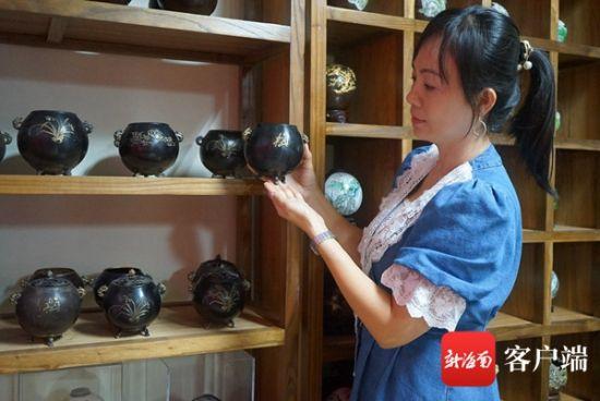 叶倩云展示陈列架上的椰壳工艺品。记者韩星 摄