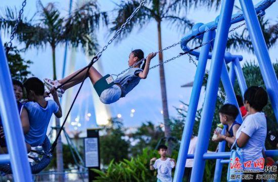 小朋友们来到海口湾公共休闲区域荡秋千玩耍。记者 康登淋 摄