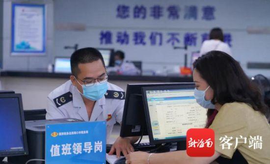 吴清春(左)在值班领导岗接待纳税人。傅启旭 摄