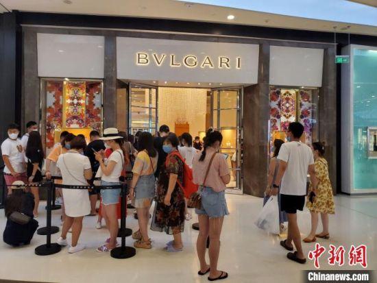 在三亚国际免税城内,顾客在一家店面外排队等待入场。 记者王晓斌 摄