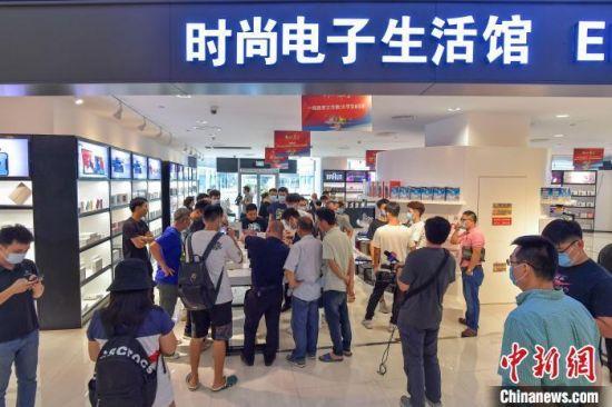 图为在海口日月广场免税店时尚电子生活馆吸引了众多民众。 骆云飞 摄