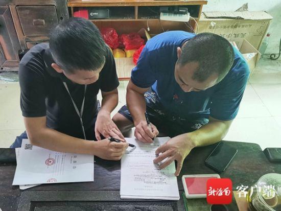 执法人员对该作坊员工吴某行(右)进行询问调查。记者 蒙健 摄