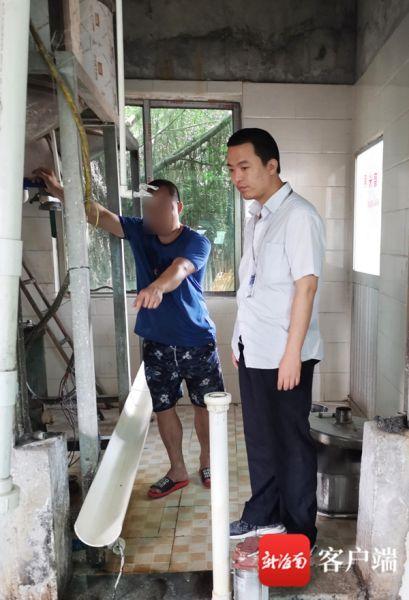 执法人员(右)对海口琼山馨骏米粉小作坊进行检查。记者 蒙健 摄