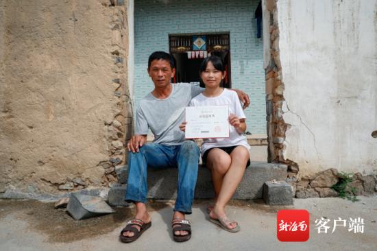 符芳如拿着大学录取通知书和父亲在家门口合影留念。记者 李昊 摄