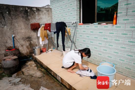 符芳如在洗父亲刚割完胶的脏衣服。记者 李昊 摄