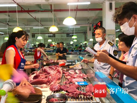 检测人员对猪肉摊位上的猪肉进行抽样送检 记者 蒙健 摄