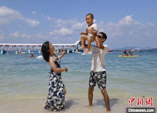 """""""十一""""期间,一家人在三亚海边嬉戏玩水。 陈宏 摄"""