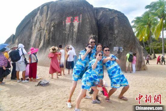 """""""十一""""期间,游客在三亚天涯海角风景区的天涯石前合影。 记者骆云飞 摄"""