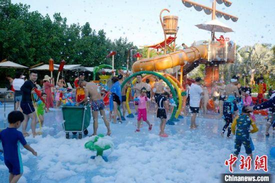 """""""十一""""期间,三亚某度假酒店泳池内,游客在漫天水泡中嬉乐。 记者王晓斌 摄"""