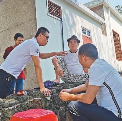 党员中心户(左前)正调解村民矛盾。 资料图片
