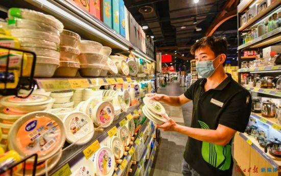 10月12日,在海口龙华路某商超,工作人员正往货架上备足全降解塑料材质的餐具。海口日报记者 王程龙 摄