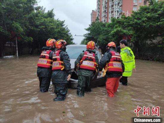 消防救援人员将被困车辆推出积水路段。 王通彬 摄