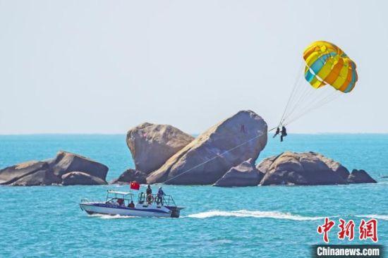 游客在天涯海角体验海上拖伞项目。 童承东 摄