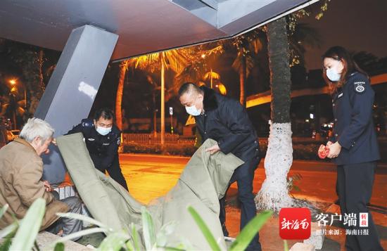 1月6日晚,在海口市大同路一店铺门口,海口市救助管理工作站工作人员给一名流浪老人系衣扣。海南日报记者 李天平 摄
