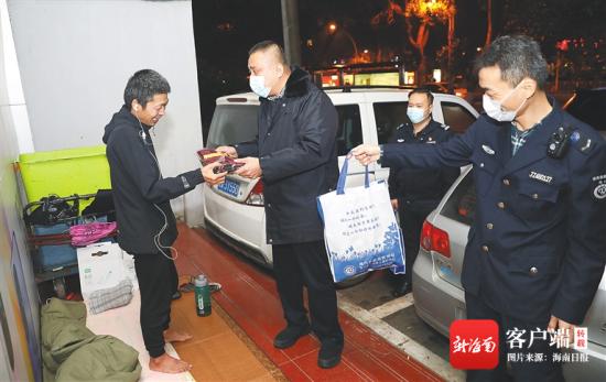 1月6日晚,在海口市大同路一店铺门口,海口市救助管理工作站工作人员为流浪人员送保暖衣物。海南日报记者 李天平 摄