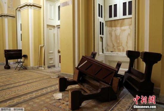 当地时间1月7日,美国华盛顿,特朗普支持者冲入国会大厦引发骚乱后,国会大厦内大量设施被损毁,现场一片狼藉。图为家具散落在走廊。